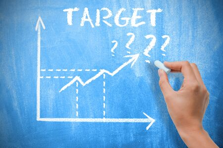 Target concept with business woman drawing growing arrows on chalkboard Stock Photo