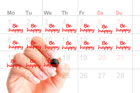 Writing in a calendar to be happy and to smile more as a wish for next year resolution