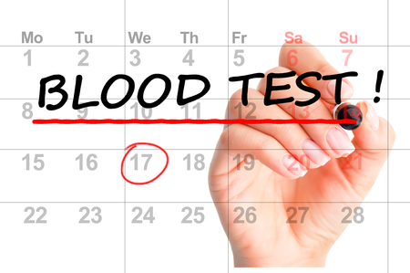 Woman hand with red marker handwriting Blood test reminder on calendar Stock Photo