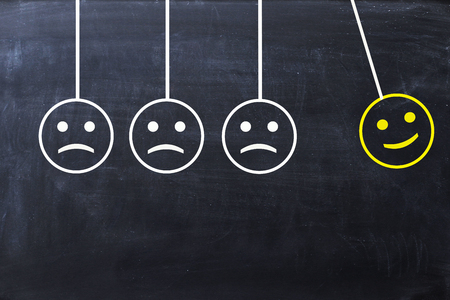 Spread happiness concept with happy and sad faces on newton's cradle on blackboard Zdjęcie Seryjne