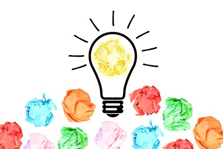Breakthrough concept with multiple colorful crumpled pieces of paper around a yellow bright light bulb shaped paper on white background