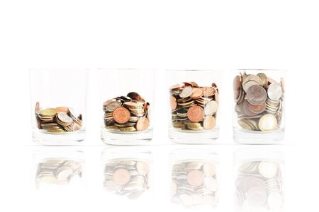 Financial growth symbolized by ascending scale of piled up coins inside glass jars isolated on white background