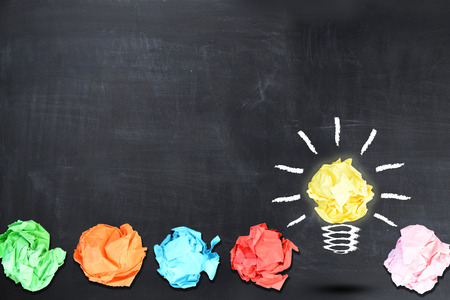 Bright idea concept with light bulb shaped crumpled paper on blackboard Stock Photo