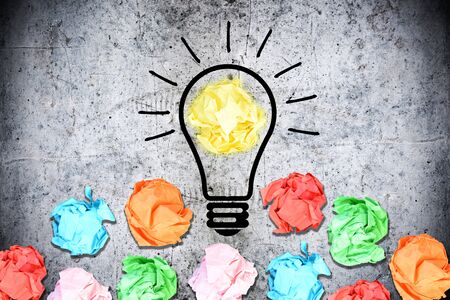 Brainstorming concept with multiple crumpled pieces of colorful paper surrounding a light bulb on concrete background Stock Photo