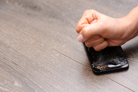 Woman hitting smartphone with her fist Stock Photo