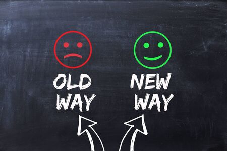 Difference between old way and new way, illustrated with happy and sad faces on blackboard Zdjęcie Seryjne - 73612049