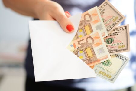Woman handing out an envelope stuffed with euros and US dollar banknotes as bribe Zdjęcie Seryjne