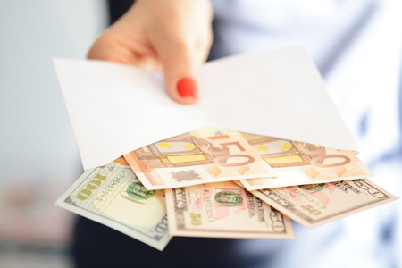 Woman handing out an envelope stuffed with euros and US dollar banknotes as bribe Stock Photo