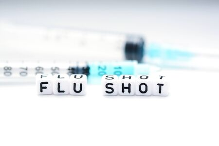 Flu shot text spelled with tiled plastic letters standing next to a syringe