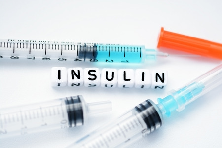 The word insulin spelled with plastic letter beads next to a syringe Zdjęcie Seryjne