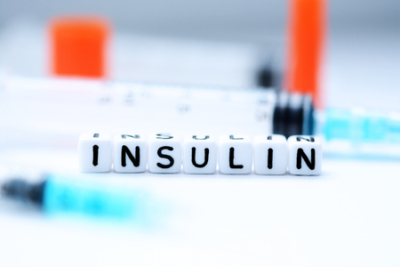 The word insulin spelled with plastic letter beads next to a syringe Banco de Imagens