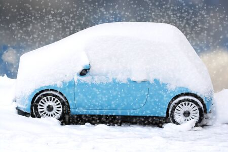 Blue car covered and surrounded by snow drifts after a snow storm
