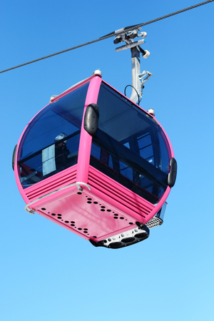 Pink cable car cabin over the snow mountain peak Standard-Bild