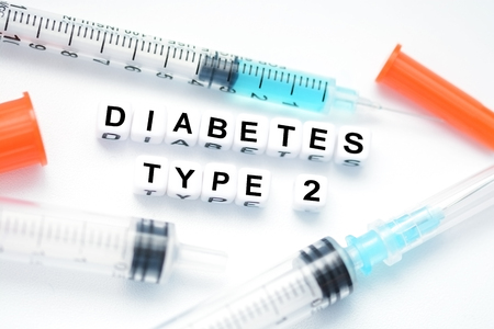 Type 2 diabetes text spelled with plastic letter beads placed next to an insulin syringe Standard-Bild