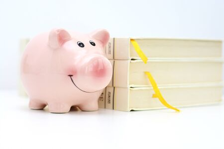Piggy bank near a pile of books suggesting saving for college concept