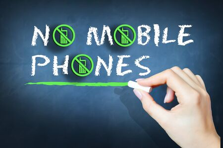 unapproved: No mobile phones handwritten text on chalkboard