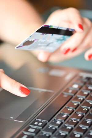 Close-up of Woman hand holding a blue credit card using an laptop for online shopping Zdjęcie Seryjne