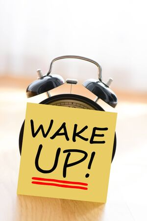 Wake up call concept with alarm clock and adhesive note