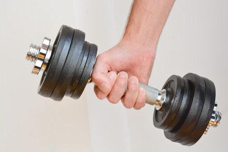 Young man doing exercises with dumbbells at home