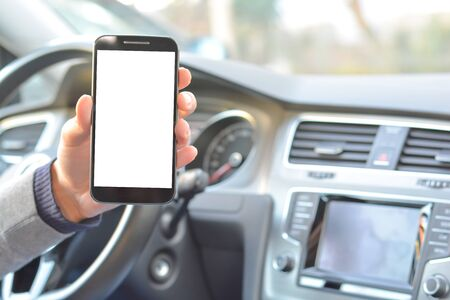 Smartphone hold by man inside a car while driving