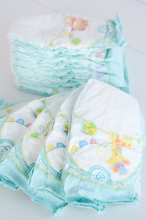 Pile or stack of baby diapers isolated on white background