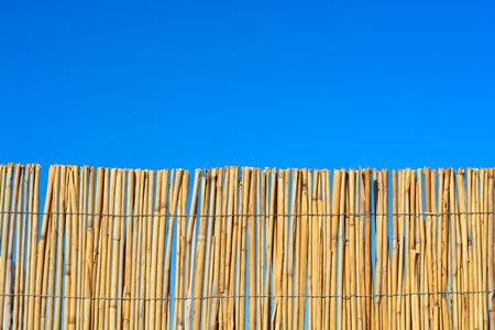Bamboo or cane fence with blue sky
