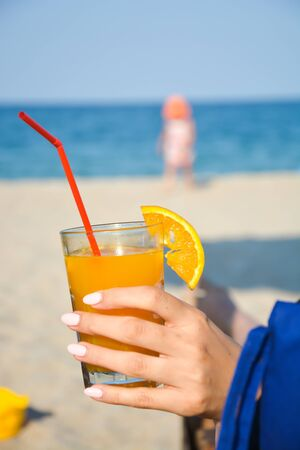 Fresh orange juice on a sunny beach in vacation Stock Photo