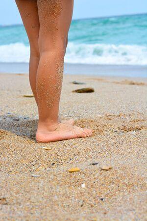 Vacation concept with woman  feet on a sunny beach Zdjęcie Seryjne