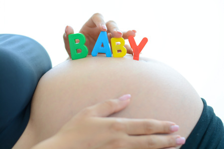 Young expectant mother with letter blocks spelling baby on her pregnant belly