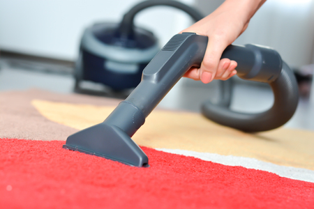 Women cleaning a red carpet with a black vacuum cleaner