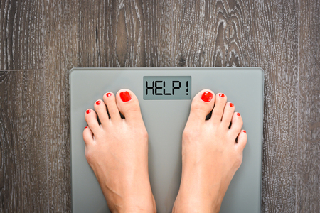 Diet problems concept with weight scale spelling HELP Standard-Bild