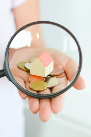 Real estate concept – coins and house architectural model in woman hand under magnifying glass Standard-Bild