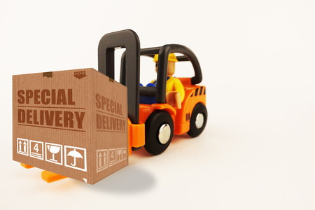 Special delivery concept with cardboard box on forklift isolated on white background Standard-Bild