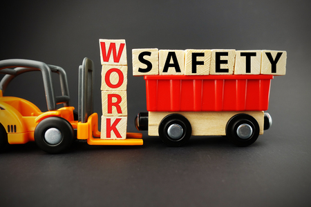 Safety at work concept with orange forklift with wooden blocks on white background
