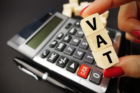 VAT calculation concept with woman hand holding vat word on wooden cubes above calculator keyboard on dark background Standard-Bild