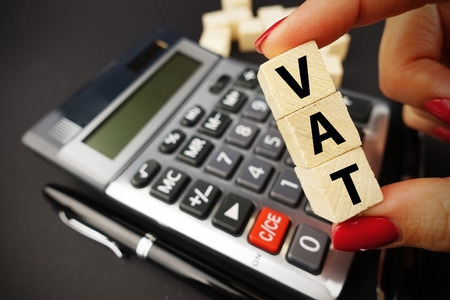 VAT calculation concept with woman hand holding vat word on wooden cubes above calculator keyboard on dark background Zdjęcie Seryjne