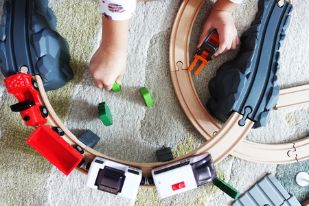 Little baby boy playing with colorful wooden train on the carpet