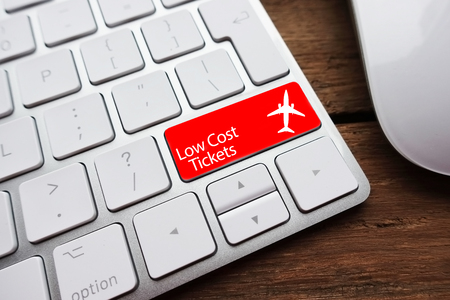 Low fare or cheap flights concept suggested by white computer keyboard with low cost tickets text on red enter key Zdjęcie Seryjne
