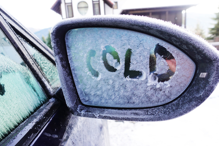 English word cold written on frozen rear view mirror