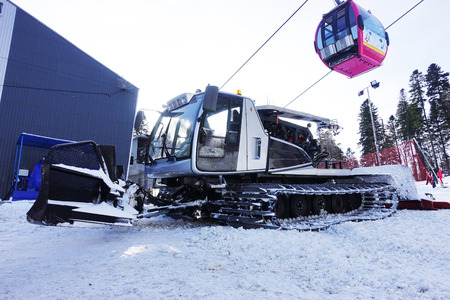 Ratrak on ski slope with pink cable car on background