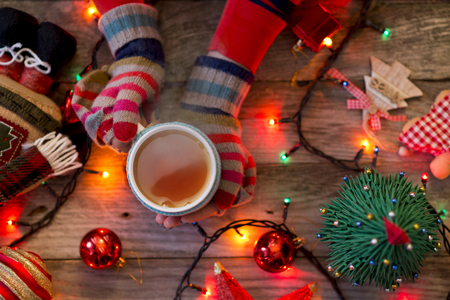 Woman's hands with colorful gloves holding a cup of hot tea in a festive Christmas décor