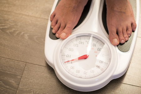 Obese or overweight male on weigh scale