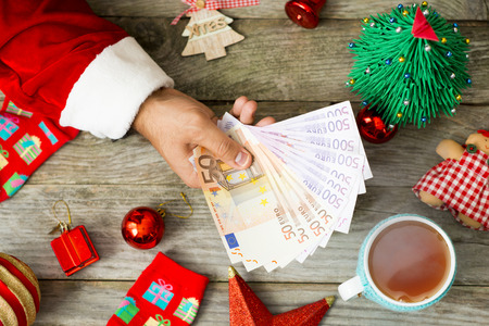 Santa Claus hand giving euro banknotes against Christmas background Zdjęcie Seryjne
