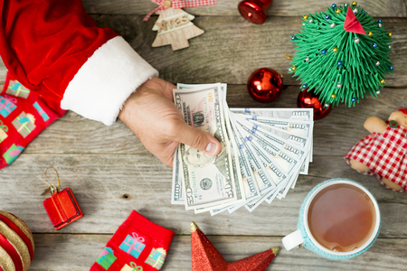 Santa Claus holding cash money against Christmas background, suggesting high expenses during the holidays Zdjęcie Seryjne