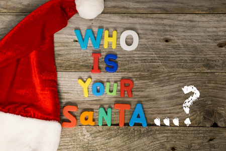 Who is your Santa question with colorful plastic letters on wooden background