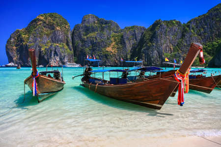 pristine corals: Long tail boat on white sand beach with crystal clear sea, Maya island, Krabi, Thailand Stock Photo