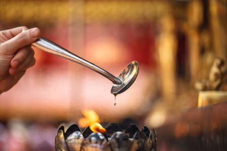 sacramental: Oil filling in Thai style metal candle in Thai temple, Chiang Mai, Thailand