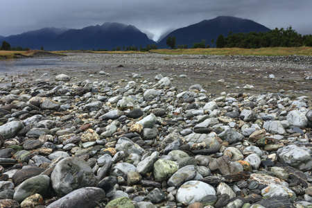 fox glacier: River from Fox glacier with rock foreground, New Zealand