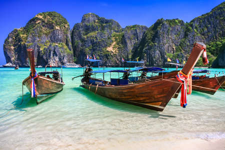 Long tail boat on white sand beach with crystal clear sea, Maya island, Krabi, Thailand photo