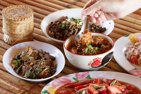 thai noodle soup: Thai launchdinner set,  curry, pork, spicay salad and sticky rice, on bamboo background Stock Photo